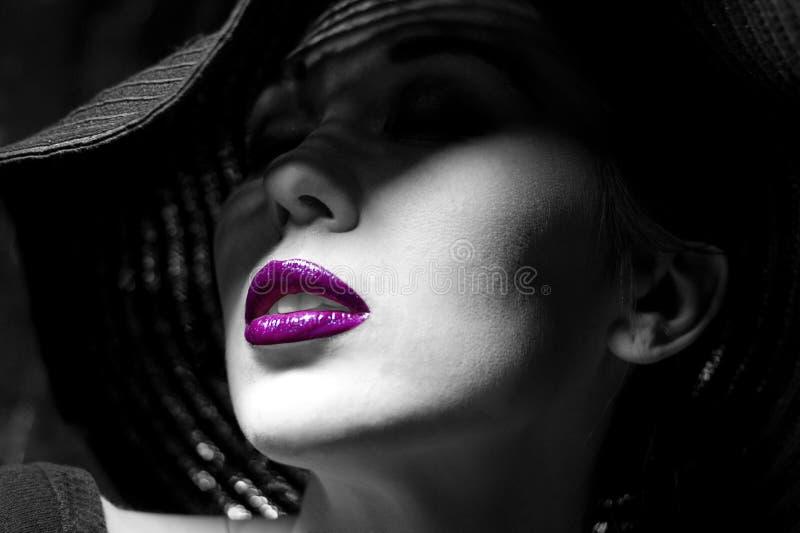 Mulher misteriosa no chapéu negro. Bordos roxos fotos de stock