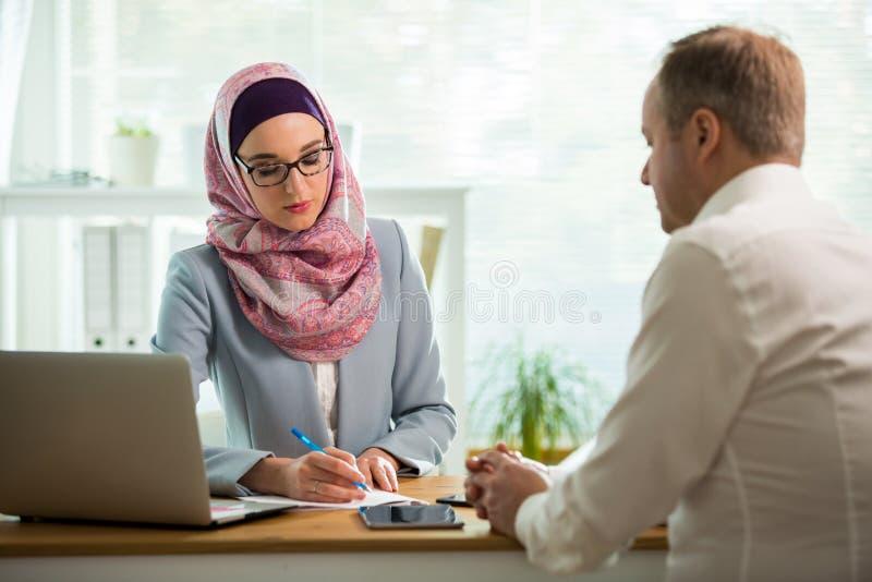 Mulher ? moda no hijab que faz a conversa??o na mesa com homem imagem de stock