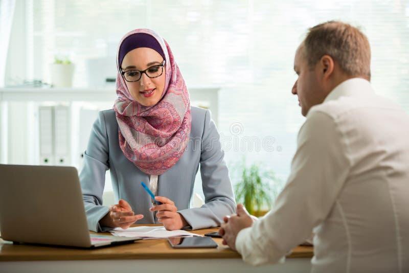 Mulher ? moda no hijab que faz a conversa??o na mesa com homem foto de stock royalty free