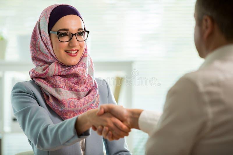 Mulher ? moda no hijab que faz a conversa??o na mesa com homem imagens de stock
