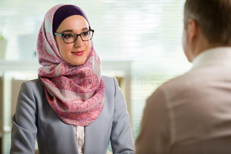 Mulher ? moda no hijab que faz a conversa??o na mesa com homem fotografia de stock royalty free