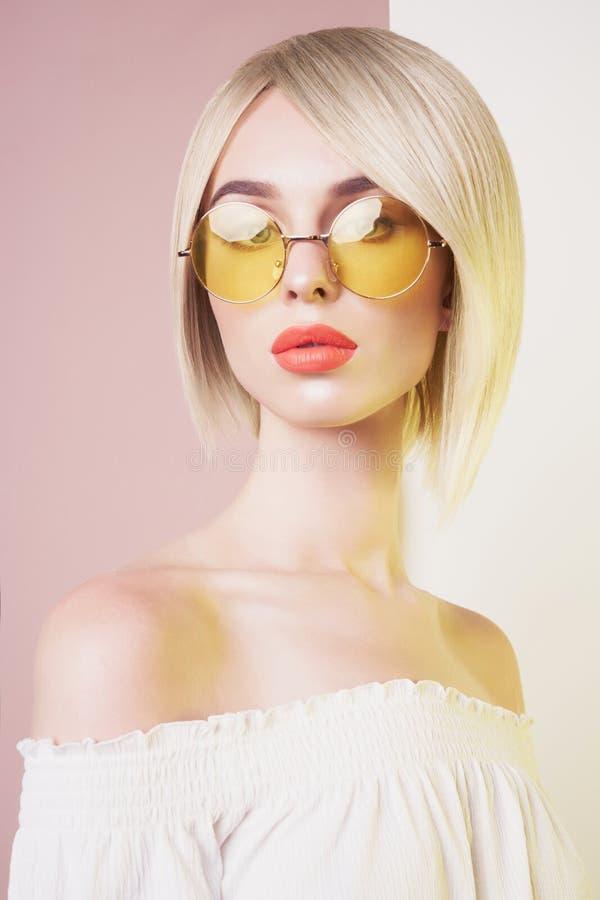 Mulher ? moda sensual no vestido branco er?tico Senhora de olhos azuis com os bordos perfeitos em ?culos de sol modernos da cor imagens de stock royalty free
