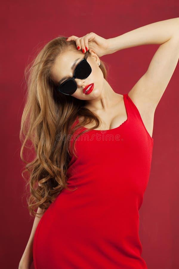 Mulher modelo bonita perfeita nos óculos de sol e no vestido vermelho Menina elegante com penteado encaracolado fotografia de stock royalty free