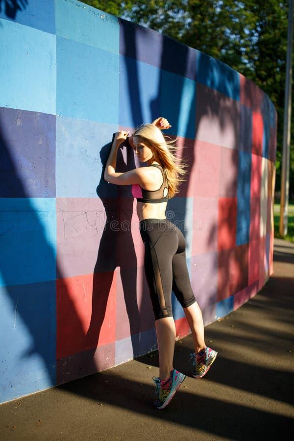A mulher modelo desportiva da aptidão durante exercícios exteriores malha Menina bonita do ajuste Estilo de vida saudável imagens de stock royalty free