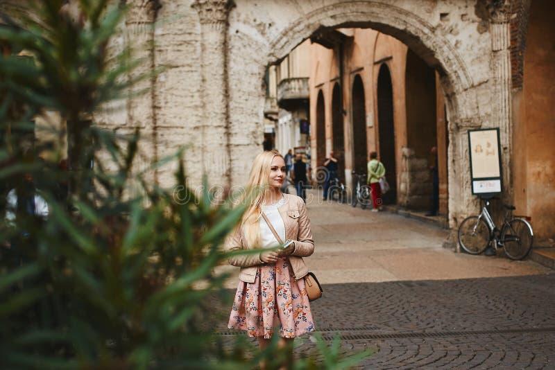 Mulher modelo loura bonita e nova em uma saia cor-de-rosa, na blusa branca e no casaco de cabedal que espera algu?m no imagem de stock
