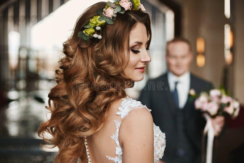 Mulher modelo moreno bonita e nova com composição brilhante e com o penteado à moda do casamento decorado com floral fotografia de stock royalty free