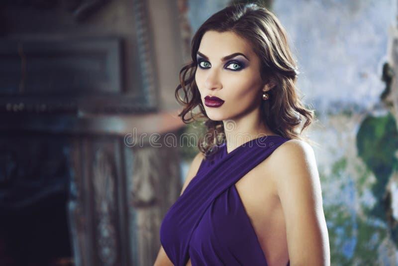 Mulher modelo moreno da beleza em nivelar o vestido roxo Composição luxuosa e penteado da forma bonita fotos de stock royalty free