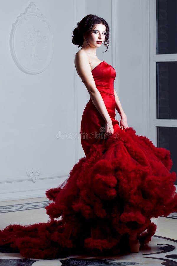 Mulher modelo moreno da beleza em nivelar o vestido vermelho Composição da forma bonita e penteado luxuosos, comprimento completo fotos de stock