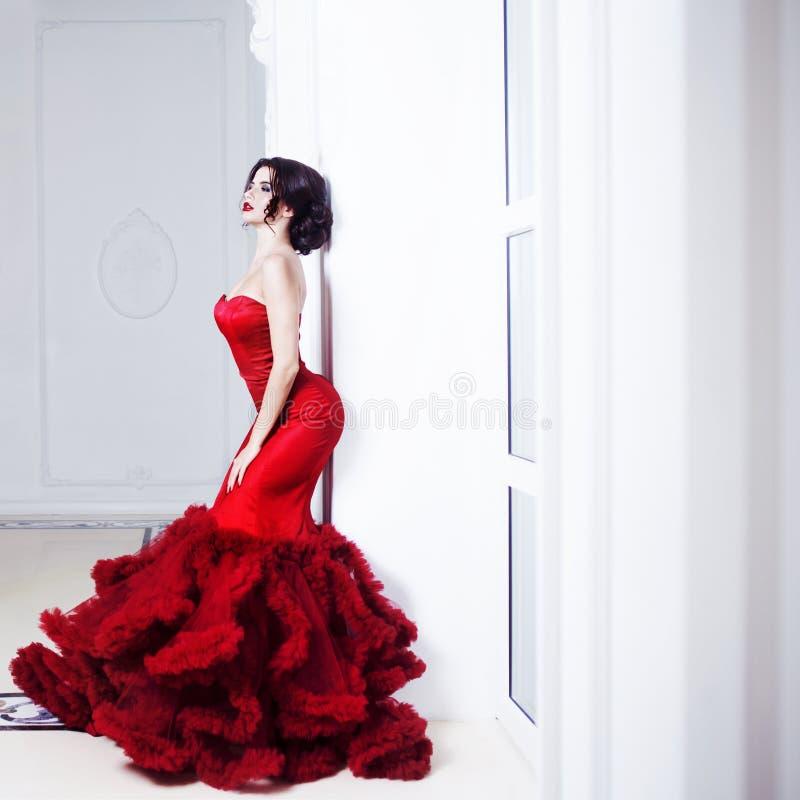 Mulher modelo moreno da beleza em nivelar o vestido vermelho Composição luxuosa e penteado da forma bonita Silhueta sedutor fotografia de stock