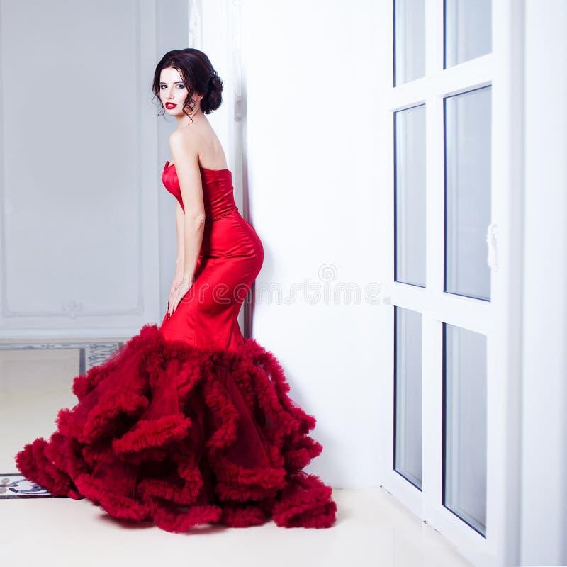 Mulher modelo moreno da beleza em nivelar o vestido vermelho Composição luxuosa e penteado da forma bonita Silhueta sedutor Uma m foto de stock royalty free