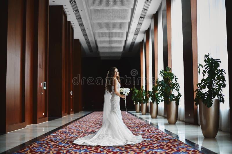 Mulher modelo moreno nova com penteado do casamento no vestido de casamento do la?o com um ramalhete de flores frescas em suas m? imagens de stock royalty free