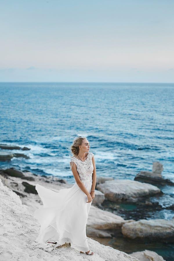 Mulher modelo nova com corpo perfeito no vestido branco longo à moda que levanta nas rochas no seacoast em Chipre imagem de stock