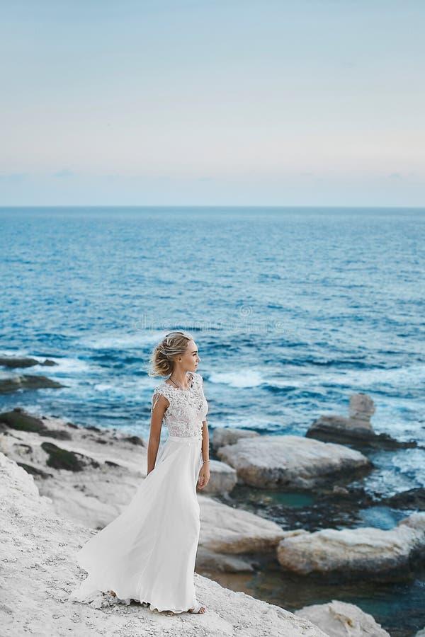 Mulher modelo nova com corpo perfeito no vestido branco longo ? moda que levanta nas rochas no seacoast em Chipre imagens de stock