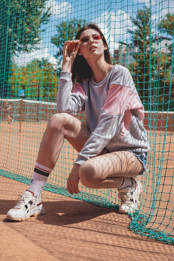 A mulher moderna à moda levanta para uma foto em uma terra de esportes no verão foto de stock