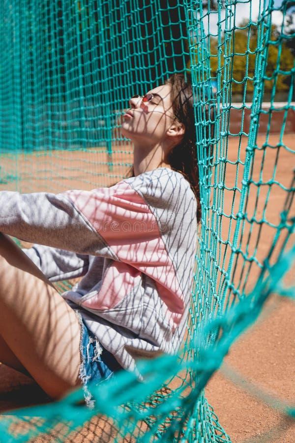 A mulher moderna à moda levanta para uma foto em uma terra de esportes no verão fotos de stock