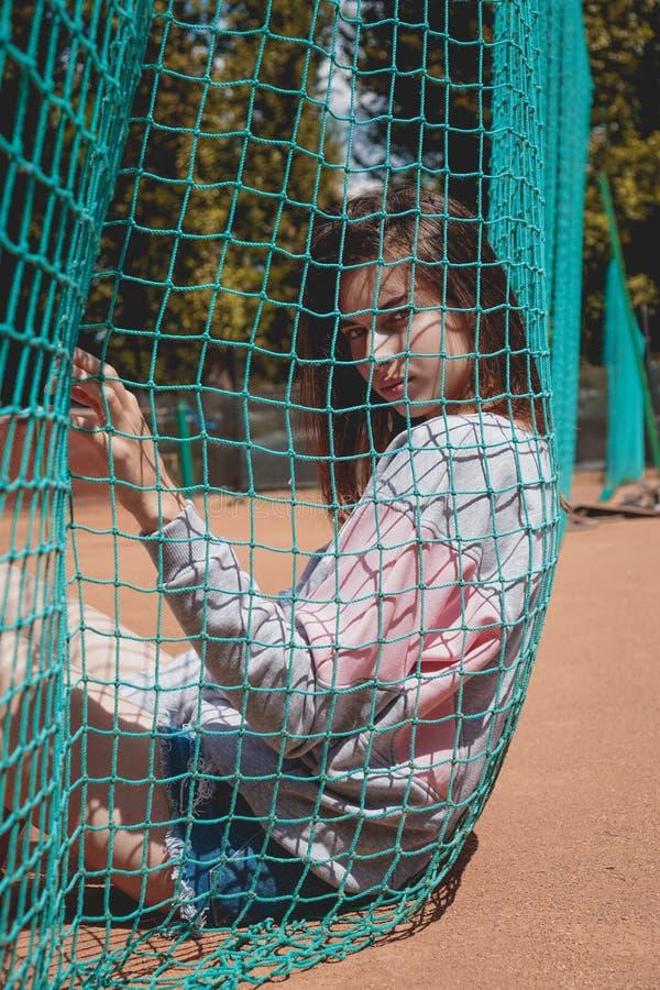 A mulher moderna à moda levanta para uma foto em uma terra de esportes no verão fotografia de stock