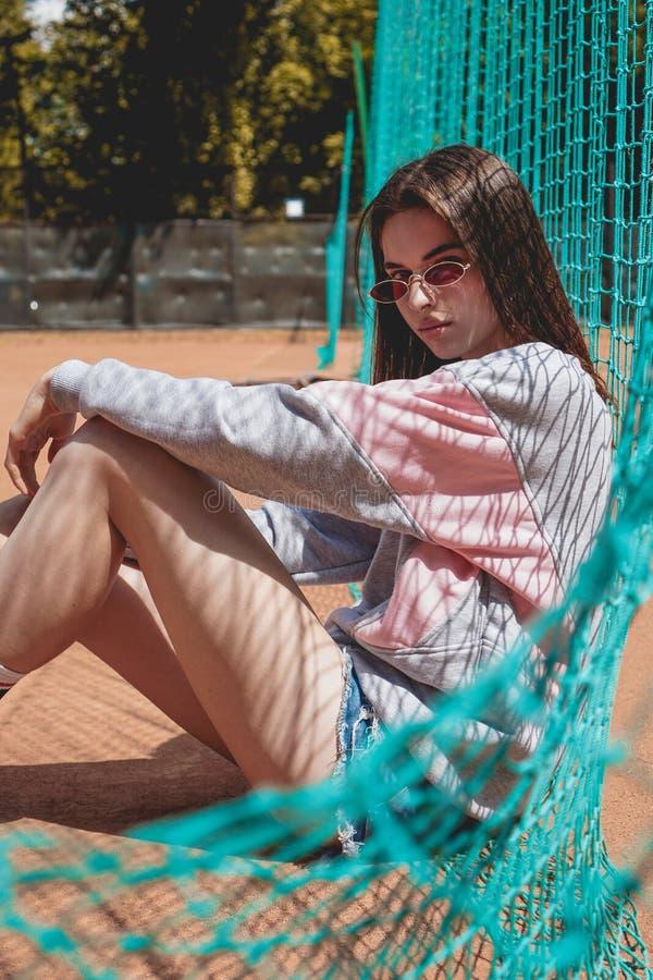A mulher moderna à moda levanta para uma foto em uma terra de esportes no verão imagem de stock royalty free