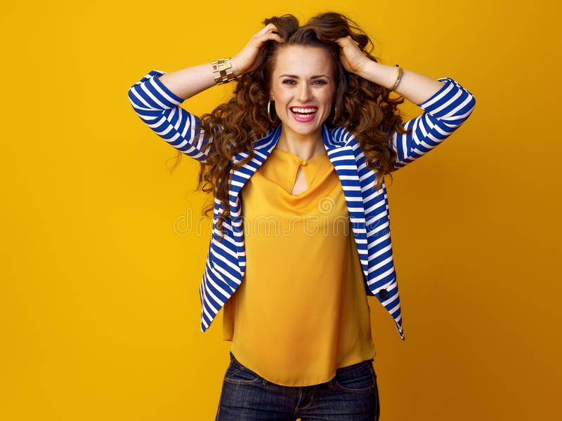 Mulher moderna alegre em revestimento listrado no fundo amarelo imagens de stock royalty free