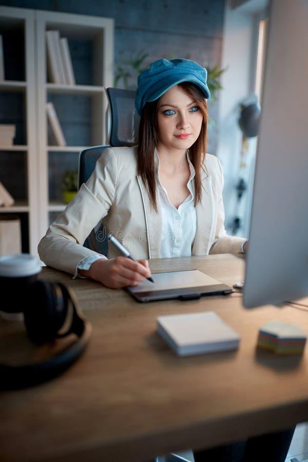A mulher moderna criativa é devotada a sua carreira e ao trabalho tarde imagem de stock royalty free