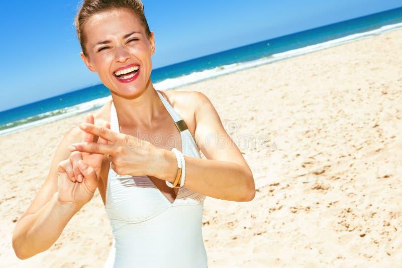 A mulher moderna de sorriso no litoral que mostra o hashtag gesticula fotos de stock royalty free
