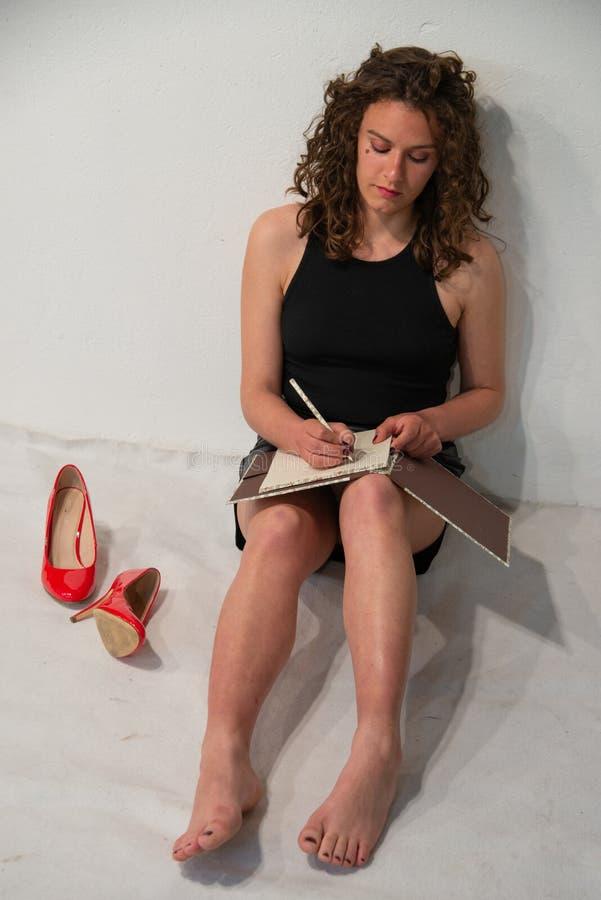 Mulher moderna do estudante da morena encaracolado nova que senta-se em uma sala toda branca imagem de stock