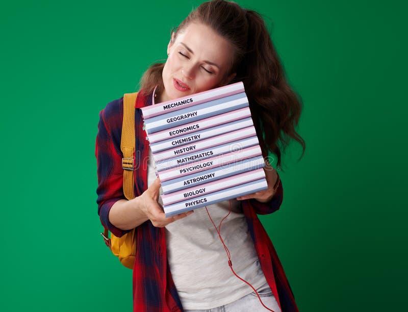 Mulher moderna do estudante que dorme na pilha dos livros imagens de stock