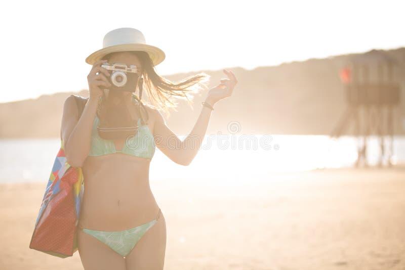 Mulher moderna na moda do moderno do ajuste atrativo que toma fotos com a câmera retro do filme do vintage Fotógrafo do estilo de fotos de stock