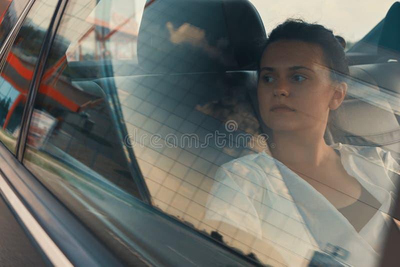 Mulher moderna que senta-se em Seat traseiro do carro na viagem por estrada que relaxa fotos de stock royalty free