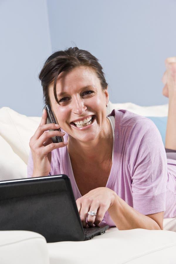 A mulher moderna relaxou no sofá com telefone, portátil imagens de stock