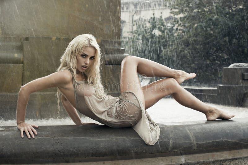Mulher molhada 'sexy' na fonte da cidade na chuva fotografia de stock