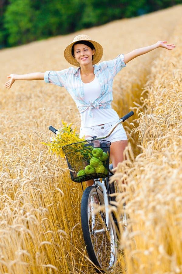 A mulher monta a bicicleta com maçãs e flores no centeio fotografia de stock royalty free