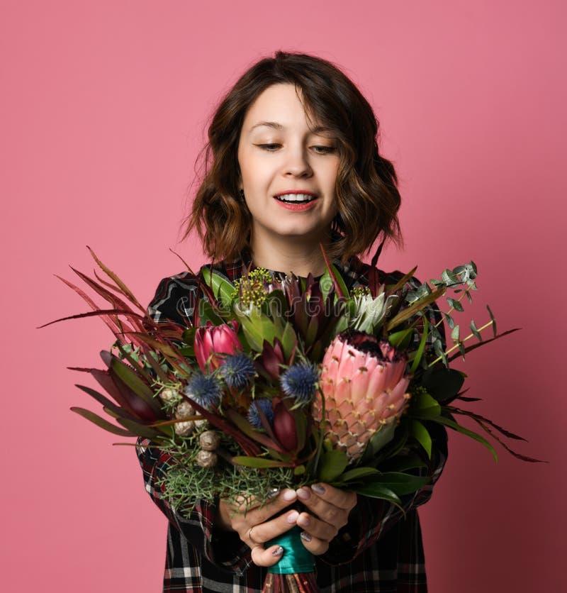 Mulher moreno atrativa dentro em um ramalhete quadriculado escuro da terra arrendada do vestido das flores na frente dela imagem de stock