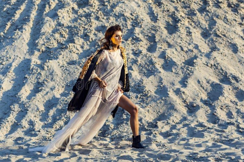 A mulher moreno atrativa na praia translúcida cobre acima com o casaco de pele do leopardo que levanta no Sandy Beach no por do s foto de stock royalty free
