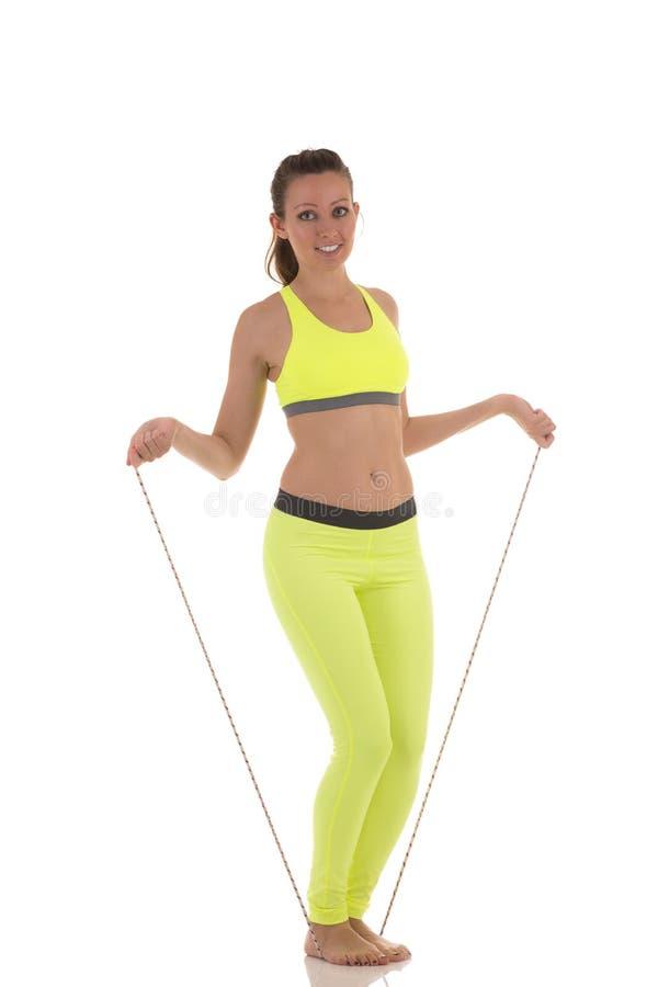 Mulher moreno atrativa nos esportes sutiã de néon e caneleiras amarelos que fazem exercícios usando uma saltar-corda longa foto de stock
