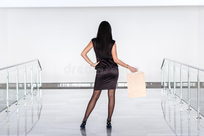 Mulher moreno atrativa nova vestida em um terno de negócio preto que guarda o saco de compras do papel, andando na alameda De vol imagens de stock