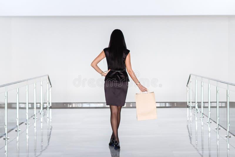 Mulher moreno atrativa nova vestida em um terno de negócio preto que guarda o saco de compras do papel, andando em uma alameda De fotografia de stock