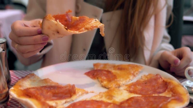 Mulher moreno atrativa que guarda a fatia de pizza e que morde a A menina com fome tem um jantar no restaurante do fast food imagens de stock