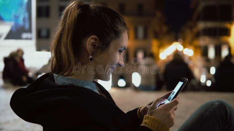 Mulher moreno atrativa que senta-se no centro de cidade na noite e que olha a foto no smartphone com tecnologia do écran sensível imagens de stock royalty free