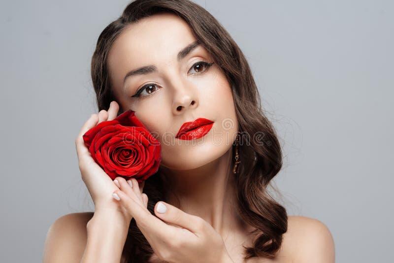 Mulher moreno bonita com batom vermelho nos bordos A menina do close-up com aumentou imagem de stock