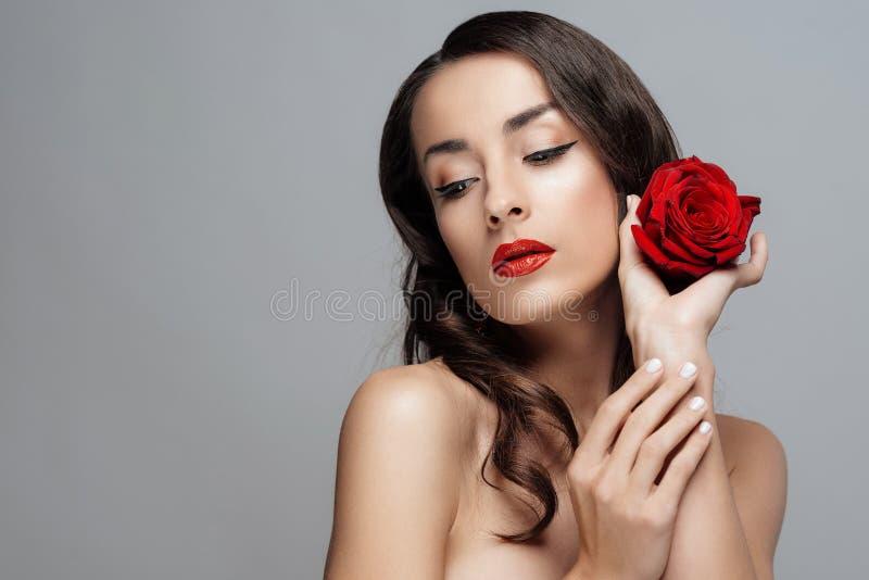 Mulher moreno bonita com batom vermelho nos bordos A menina do close-up com aumentou foto de stock royalty free