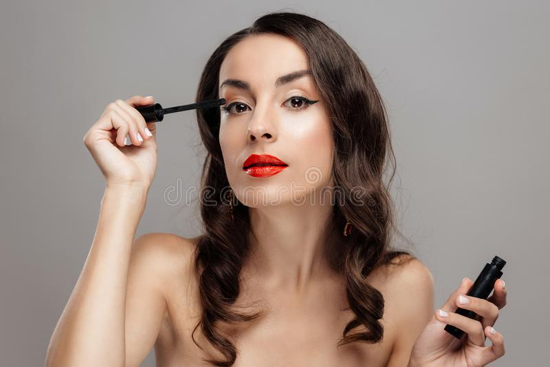 Mulher moreno bonita com batom vermelho nos bordos Menina do close-up com composição bonita imagens de stock