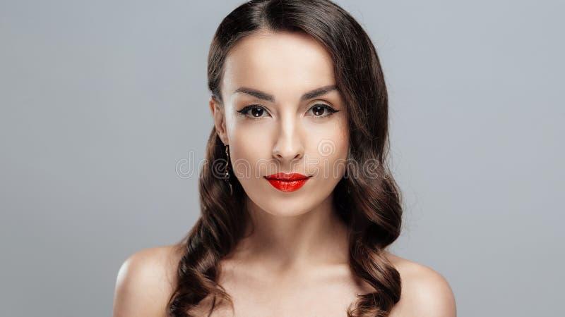 Mulher moreno bonita com batom vermelho nos bordos Menina do close-up com composição bonita fotos de stock royalty free
