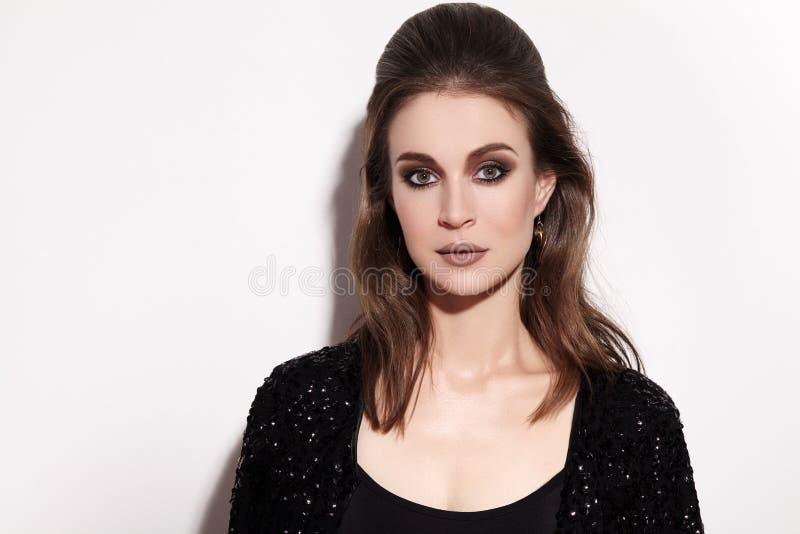 Mulher moreno bonita com composição da forma no fundo branco Comemore o estilo, revestimento preto da faísca, penteado imagens de stock