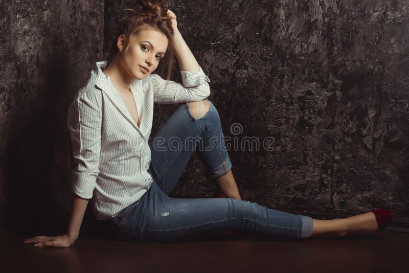 Mulher moreno bonita com composição natural na camisa e no brim rasgado fotos de stock royalty free
