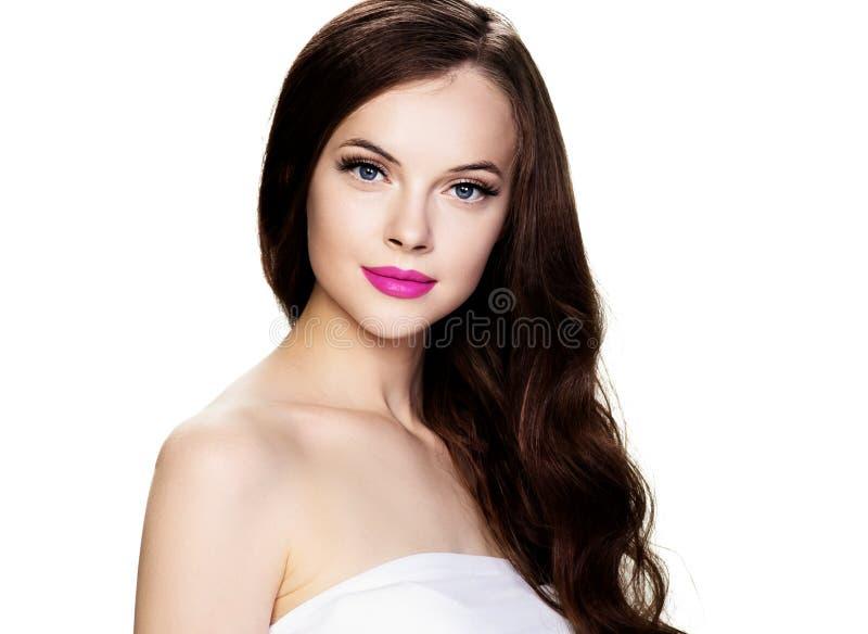 Mulher moreno bonita com extensão das pestanas e batom encaracolado moreno longo do rosa do penteado imagens de stock royalty free