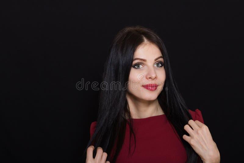 A mulher moreno bonita com olhos azuis em um fundo escuro guarda seu cabelo imagens de stock royalty free