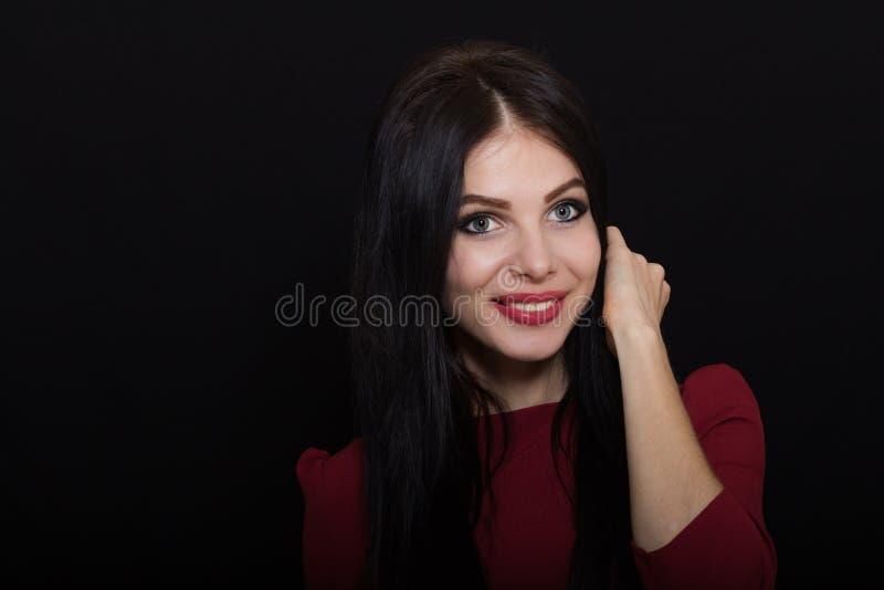 A mulher moreno bonita com olhos azuis em um fundo escuro guarda seu cabelo fotos de stock