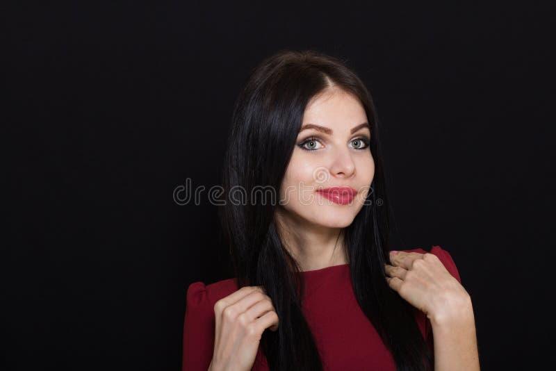 A mulher moreno bonita com olhos azuis em um fundo escuro guarda seu cabelo fotos de stock royalty free