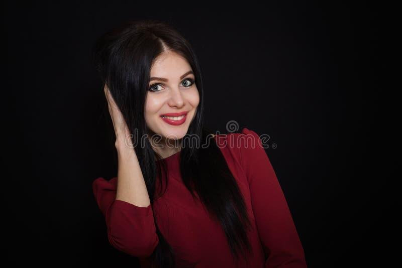 A mulher moreno bonita com olhos azuis em um fundo escuro guarda seu cabelo foto de stock royalty free
