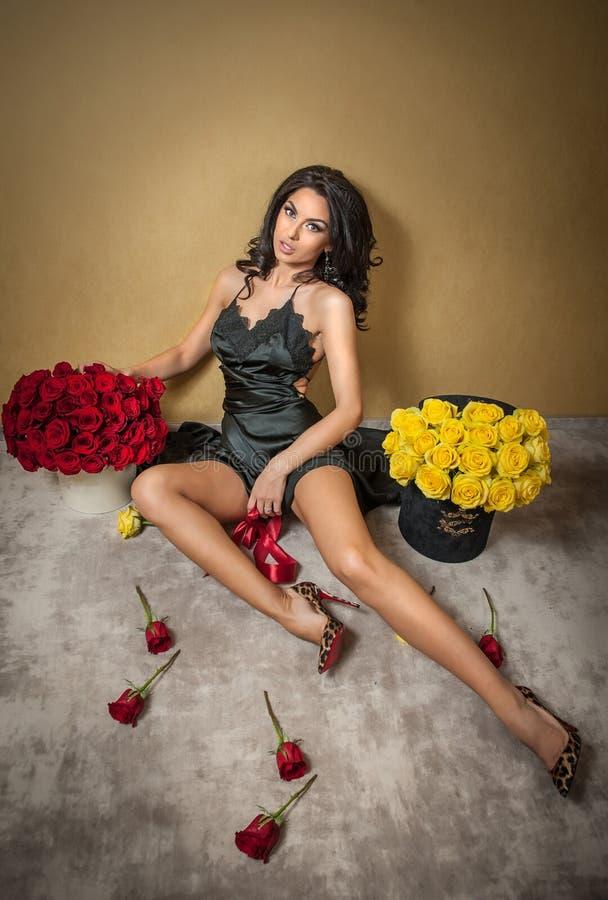 Mulher moreno bonita com os ramalhetes de muitas rosas vermelhas e amarelas no apartamento interior, dia de Valentim Senhora atra foto de stock royalty free